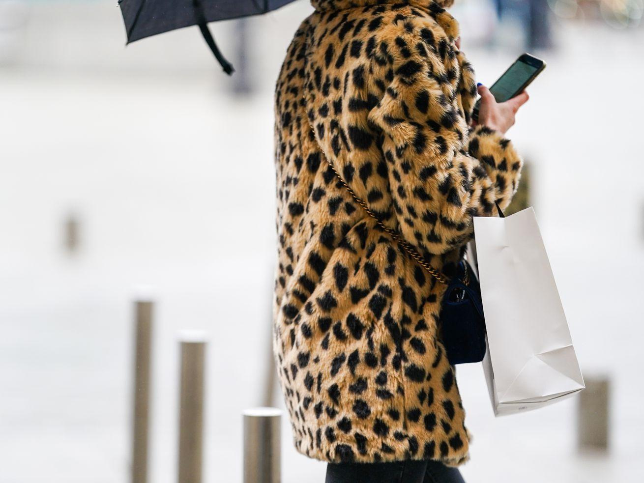Une femme dans les rues de Paris porte un manteau en fausse fourrure à imprimé léopard.