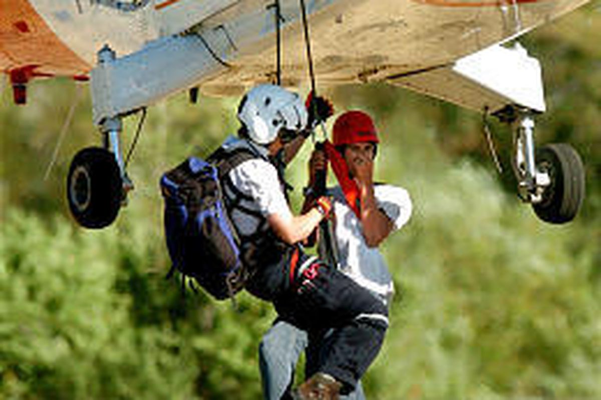 A teen, right, who was lost overnight with his dad, is hauled aboard helicopter in Deaf Smiths Canyon area.