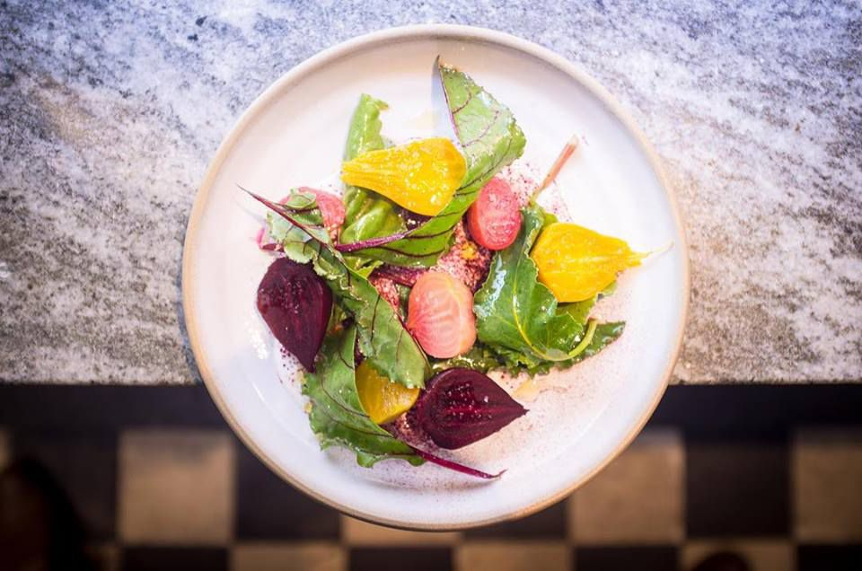 From above, a plate of beets with greens hangs off a countertop