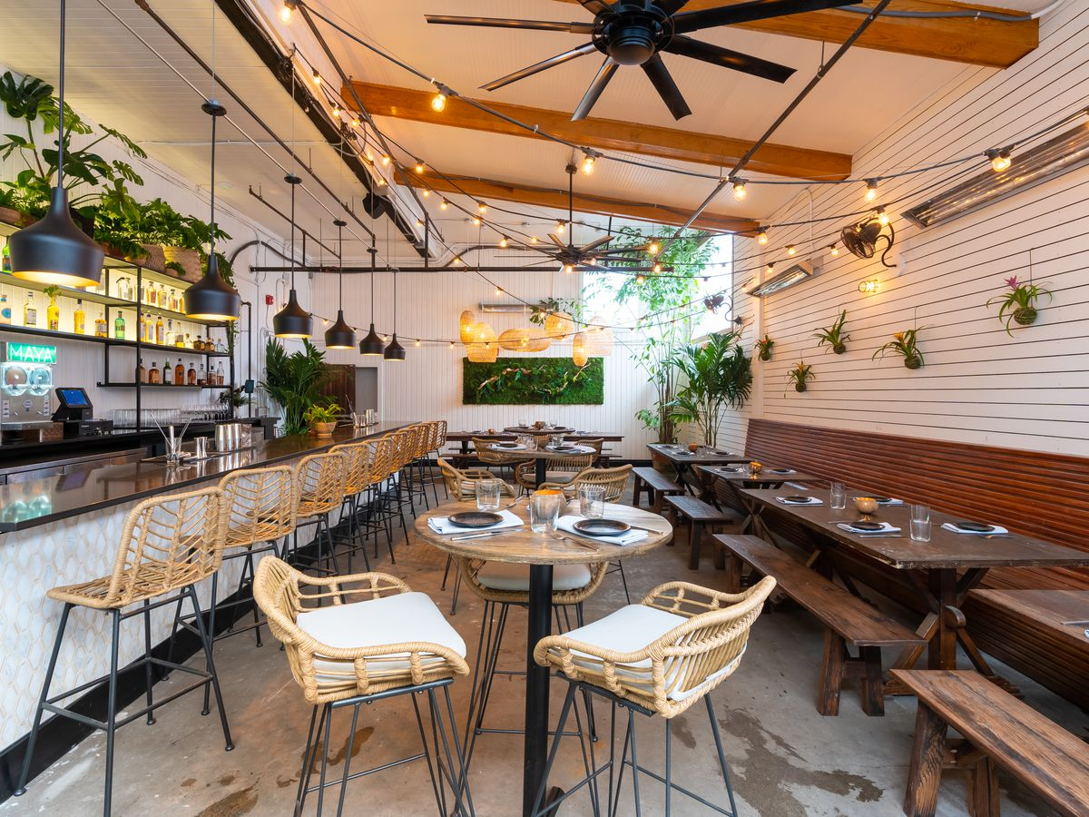 Outdoor tables surrounded by greenery.