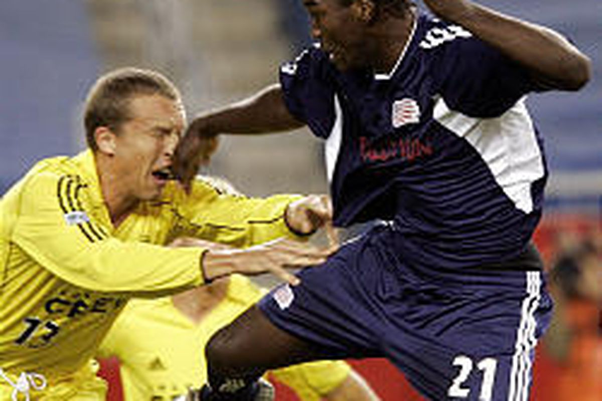 New England's Shalrie Joseph, right, pushes away Columbus Crew's Mark Schulte.