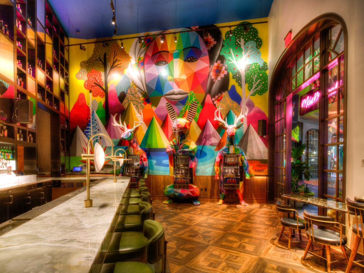 Mama Rabbit's bar area, mural, and slot machines