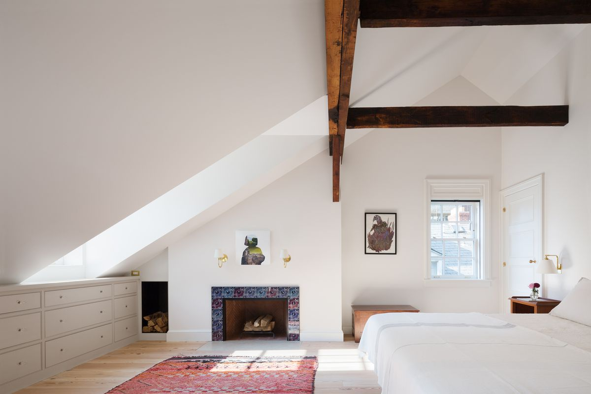 A bedroom. There are exposed wooden beams on the ceiling. There is a large bed with white bed linens. There is a fireplace which has a colorful mosaic frame and logs sitting inside. The walls are painted white and there is artwork hanging.