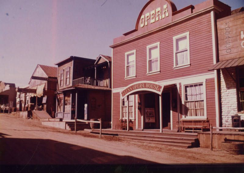 An archival image of an old Western movie set. Wood-clad buildings line a dusty road. One is an opera house.