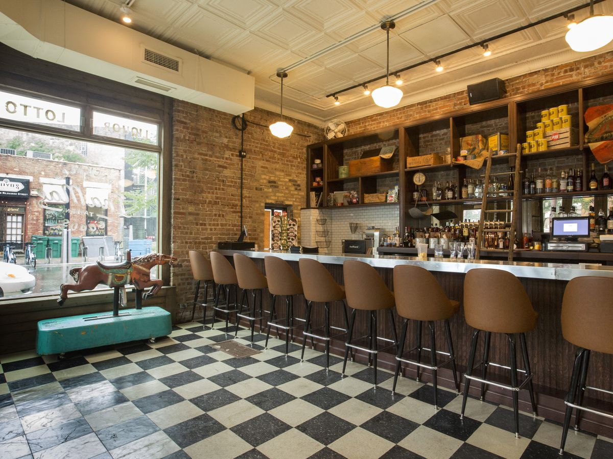 A bar with stools and a distressed checkered floor.