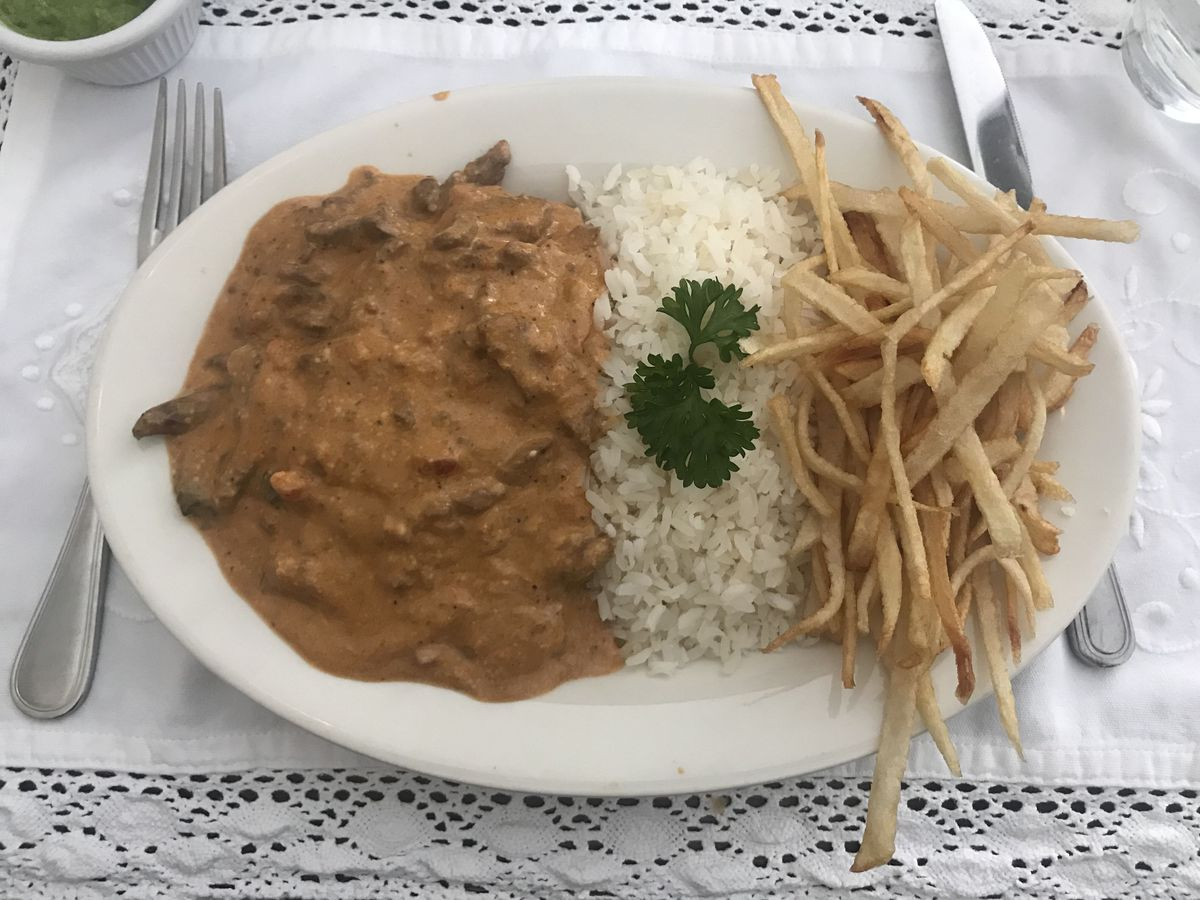 A plate topped with three equal parts of beef stroganoff, white rice topped with cilantro, and potato sticks