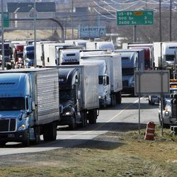 One truck is on its side at right due to wind as other trucks get off the northbound Centerville exit, Thursday, Dec. 1, 2011.