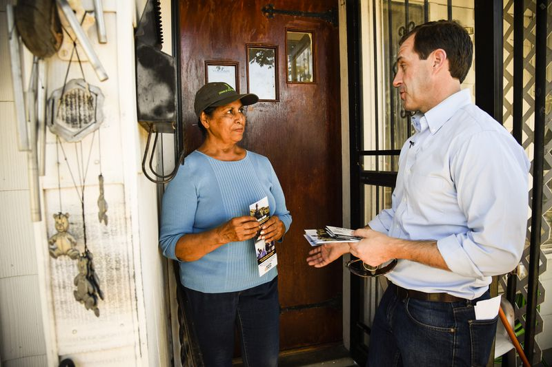 Jason Crow, 6th Colorado congressional district candidate, talks with Maria Valle on her front porch on September 15, 2018.