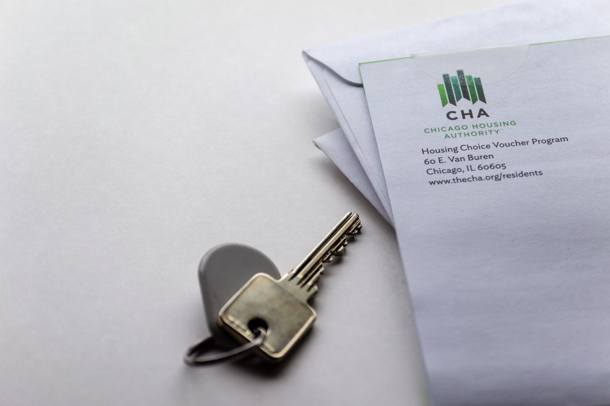 A set of two silver keys on a ring next to a white envelope with blue and green Chicago Housing Authority logo in the corner.