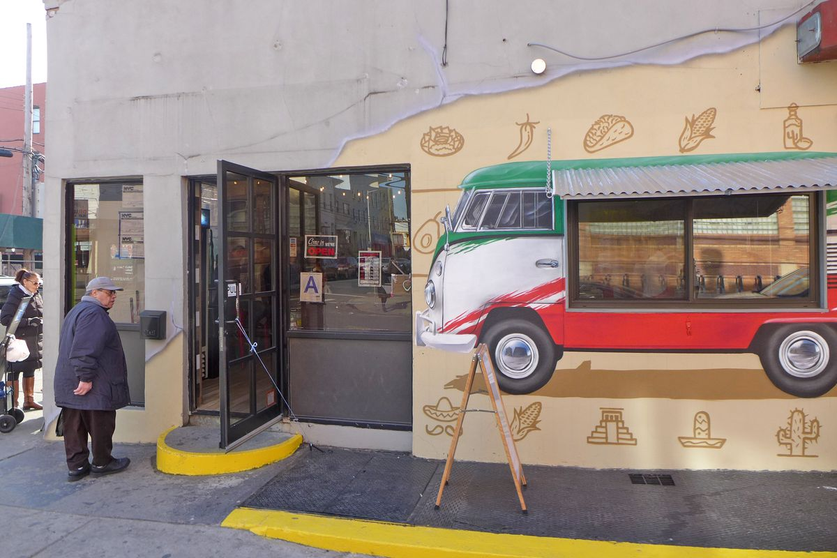 A gray storefront has a colorful VW microbus taqueria painted on the outside.