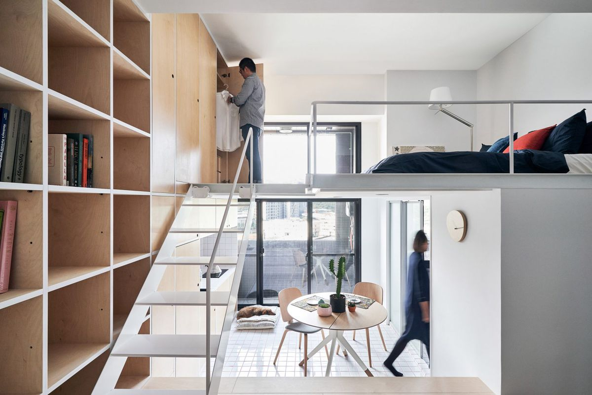 This compact apartment features a living room in the entrance to the home with a kitchen down the steps just beyond, while the bedroom sits lofted above, accessible via a moveable ladders. To the left, a birch wood storage wall offers shelving, cupboards,