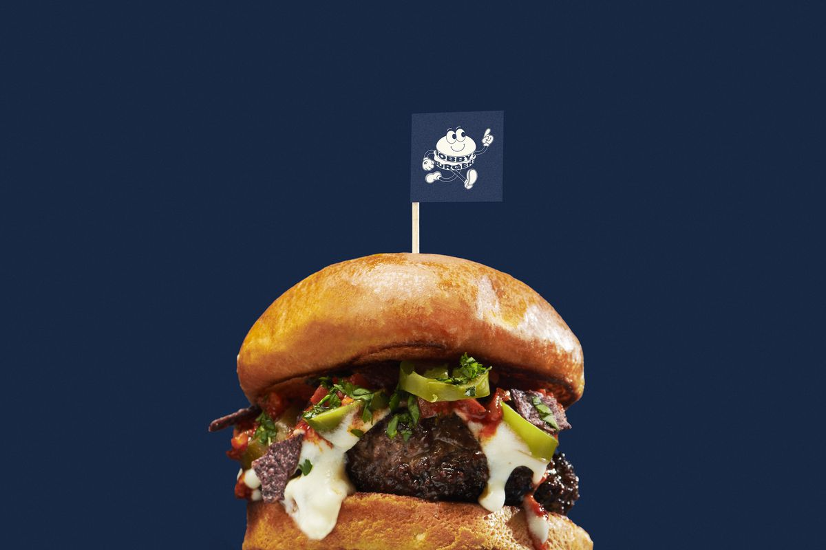 A hamburger with cheese and a flag on top