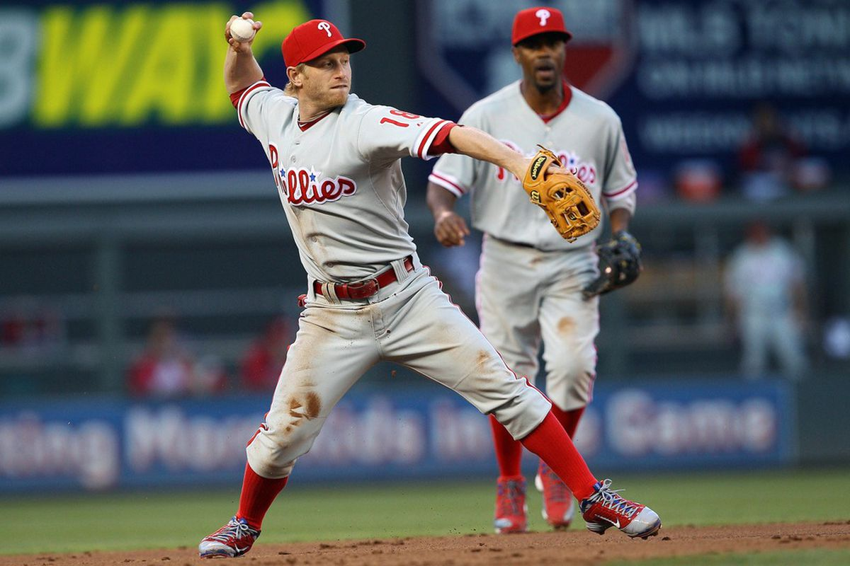 June 12, 2012; Minneapolis, MN, USA: Philadelphia Phillies second baseman Mike Fontenot (18) throws the ball to first base in the third inning against the Minnesota Twins at Target Field. Mandatory Credit: Jesse Johnson-US PRESSWIRE