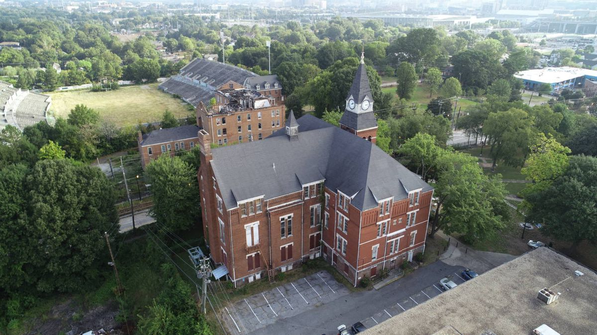 A drone photo of an old brick building and abandoned football stadium in the distance.