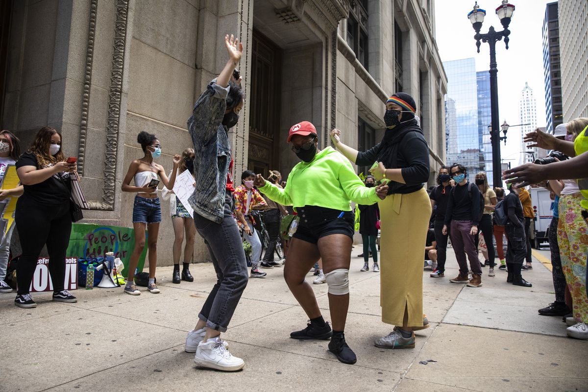 Protesters calling for the city to defund the Chicago Police Department dance at a rally outside City Hall in the Loop, Tuesday afternoon, Aug. 18, 2020. | Ashlee Rezin Garcia/Sun-Times