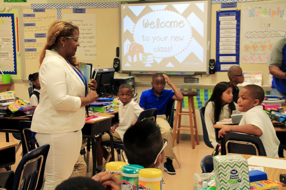 A third-grade teacher at Bruce Elementary welcomes her class on the first day of school.