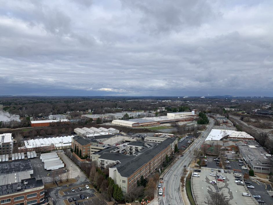 A view over buildings to trees and a gray sky.