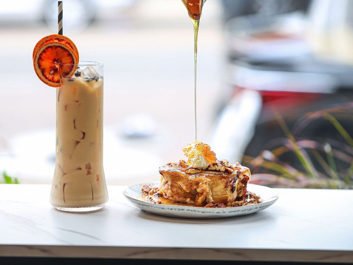 A tall creamy cocktail next to a plate of French toast with syrup being poured on top.