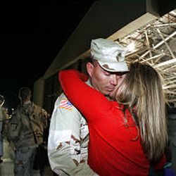 Sgt. William Stock of the 148th Field Artillery is met with a hug and kiss from his girlfriend, Leanne Turner, at a National Guard base on Friday.