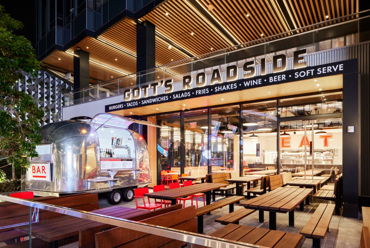 The exterior of Gott's at Chase Center with wooden community tables and a trailer on the outdoor patio.