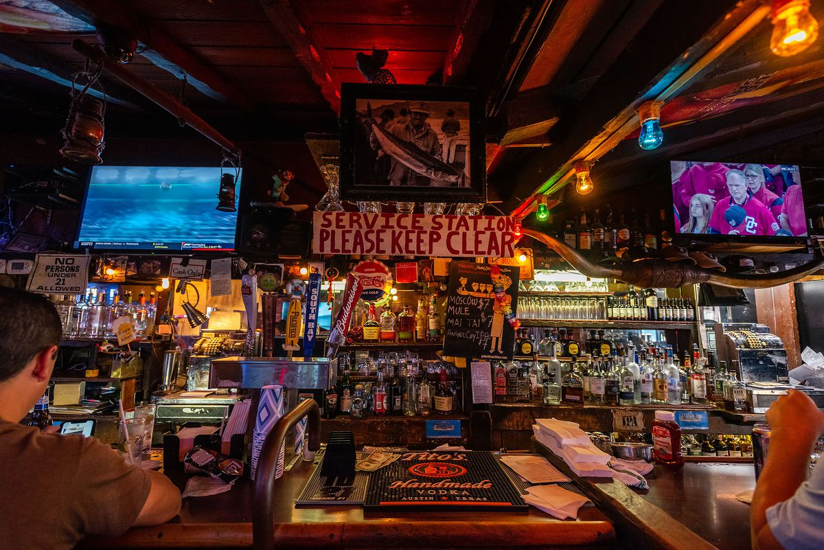 An ordering station at a dim, red-tinged dive bar.