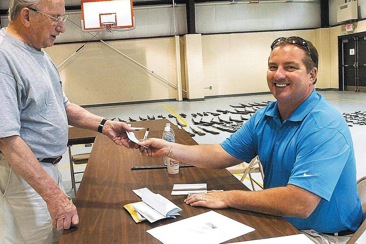 FILE - This June 27, 2009 file photo, Central Falls, R.I. Mayor Charles Moreau, right, hands a check to Roger Dupont, of West Warwick, R.I. for a handgun during a gun buy-back program at the Wyatt Detention Center in Central Falls, R.I. Moreau resigned an