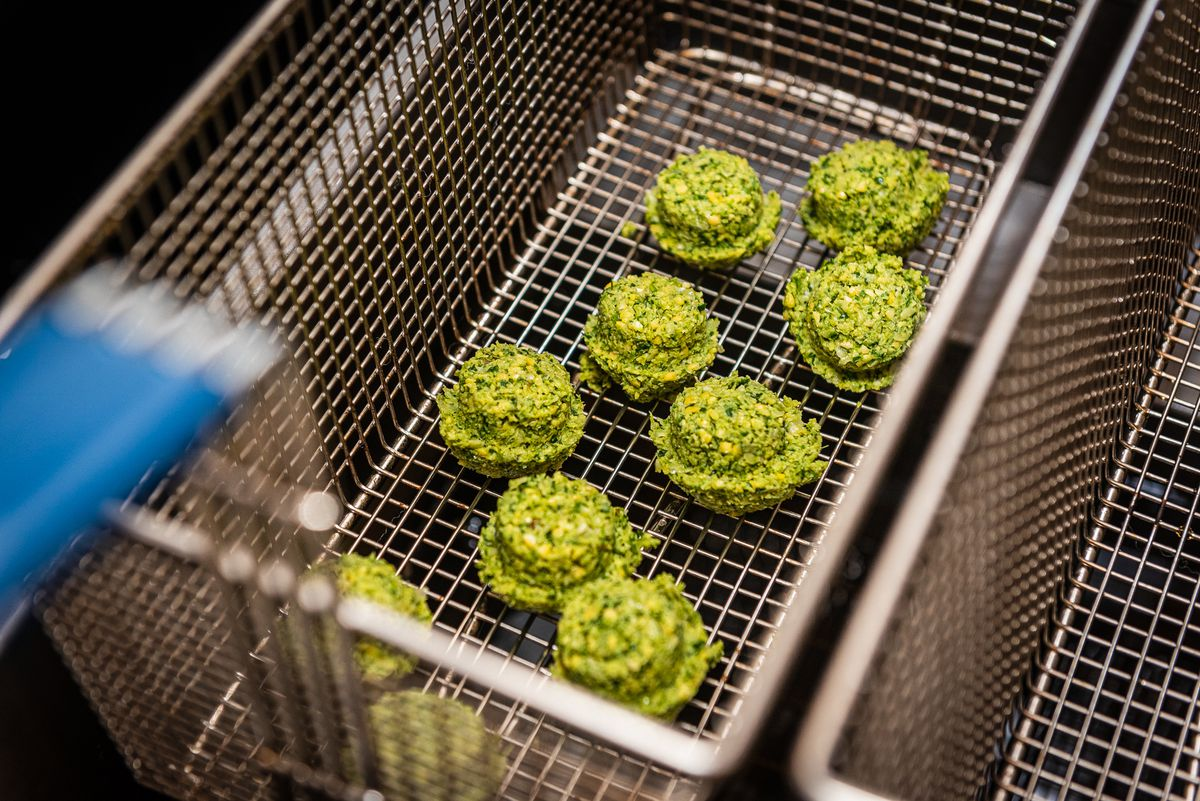 Green falafel balls about to be dunked in the fryer