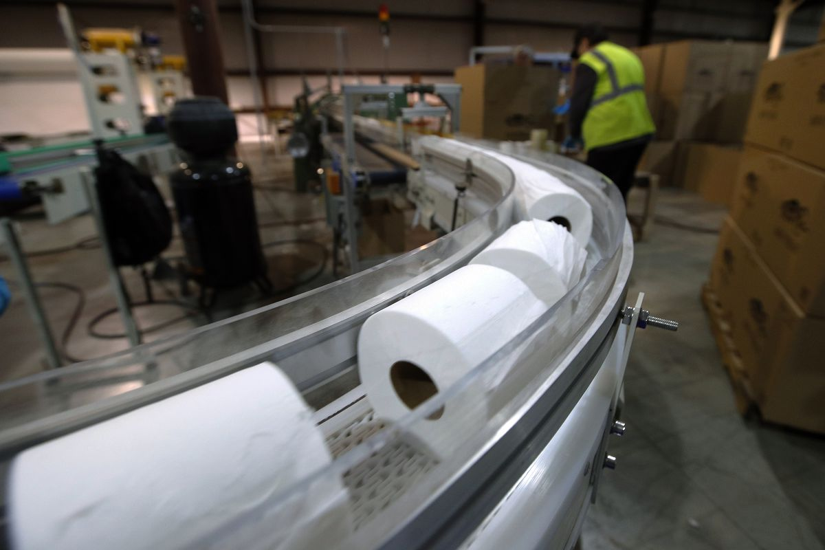 Toilet paper moves out from a cutting machine at a factory in Maine.