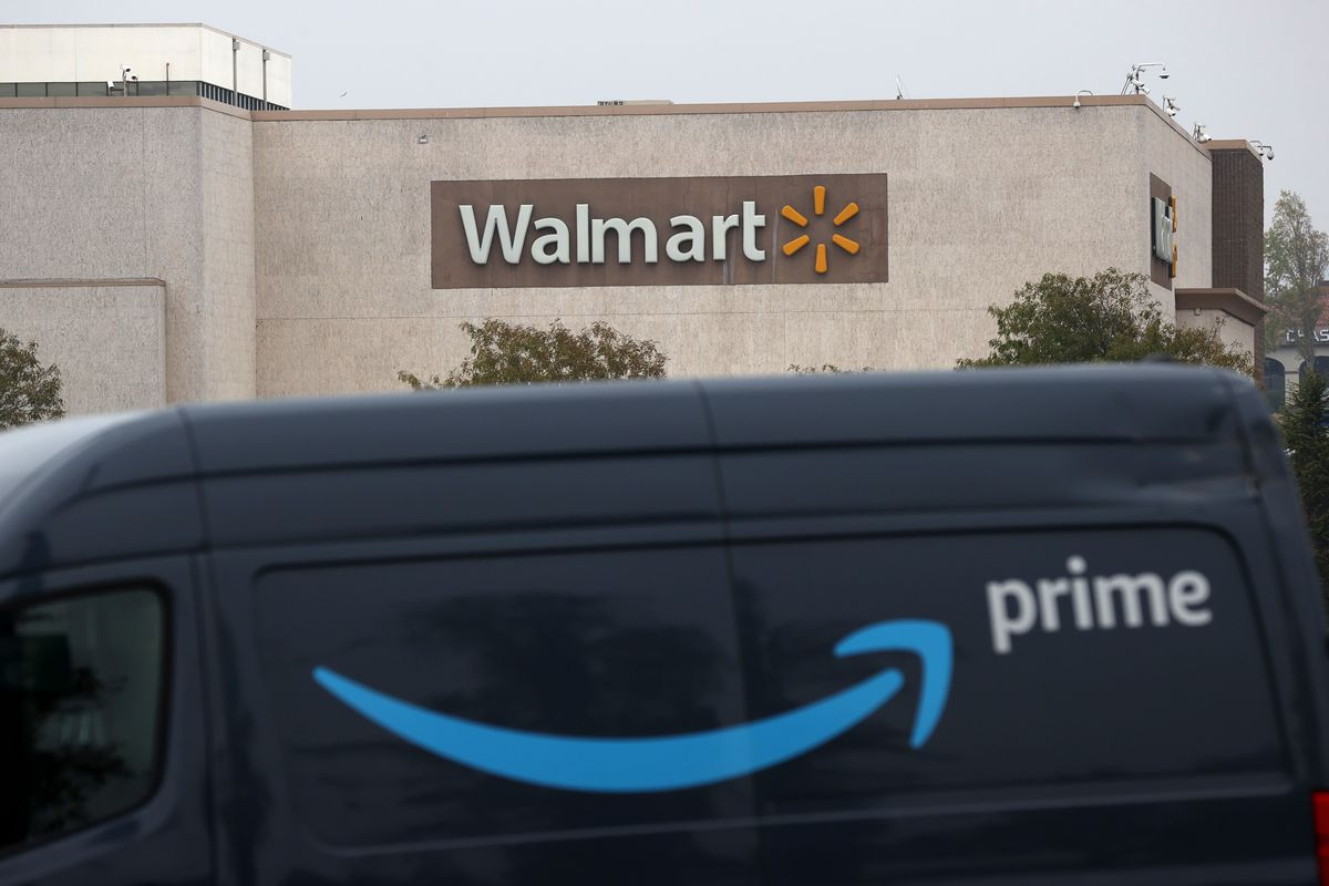 An Amazon Prime delivery van parked outside a Walmart store.