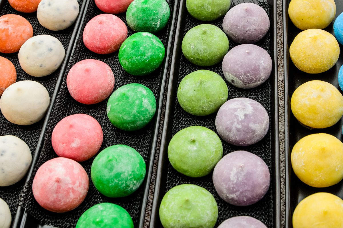 Black trays are filled with little balls of colorful mochi