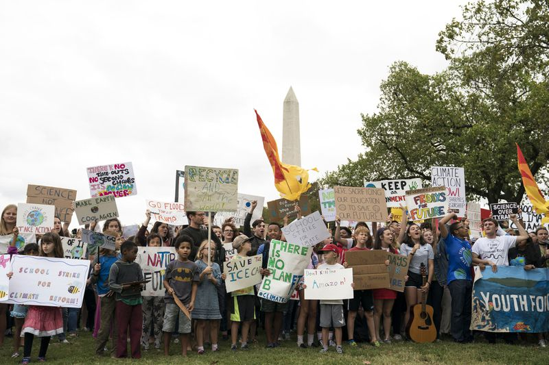 Young students protest climate change with the Washington monument in the background.