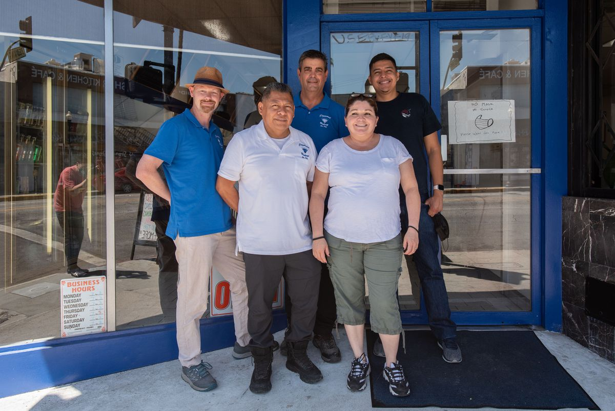 Five employees in different shirts stand in the shaded entryway of an aging bakery.