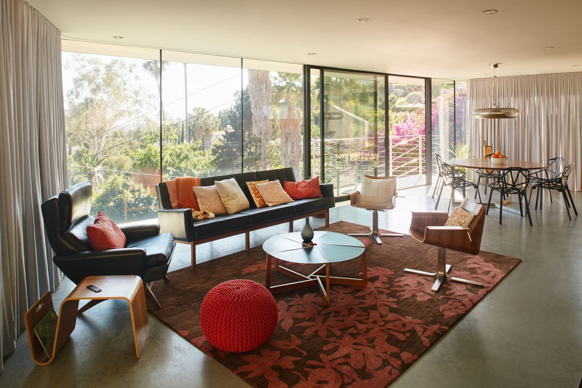 At A Concrete Ciffside Home In La An Area Rug Plays Up The E S Accent Colors While Adhering To Trick Of Putting Front Legs And Side Chairs On