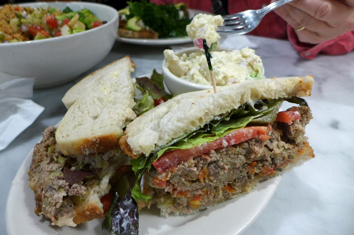 A thick meatloaf sandwich on white bread is seen, cut face outward, with a bowl of potato salad in the background...
