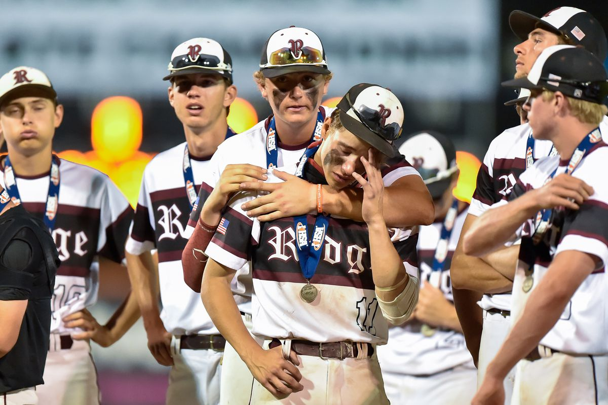 Prairie Ridge's Dylan Bremer (11) is consoled by teammates after the game against Springfield.
