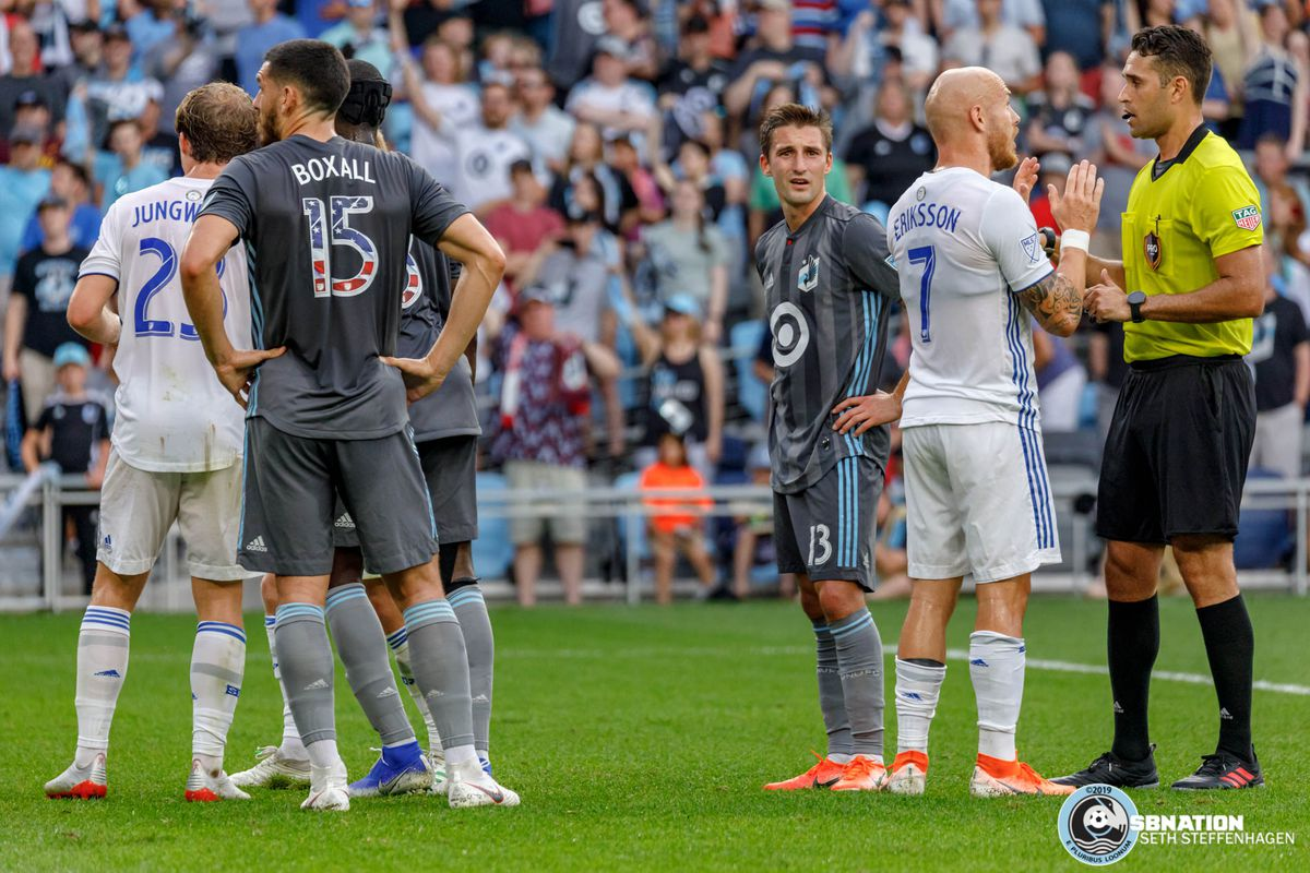 July 3, 2019 - Saint Paul, Minnesota, United States - Minnesota United midfielder Ethan Finlay (13) listens in as San Jose midfielder Magnus Eriksson (7) gets into an argument with referee Marcos DeOliveira during the match at Allianz Field.