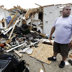 Juan Ventura Jr., stands in the middle of his tornado damaged home as he works to save personal items from the destruction Wednesday, April 4, 2012, in Forney, Texas.  (AP Photo/Tony Gutierrez)