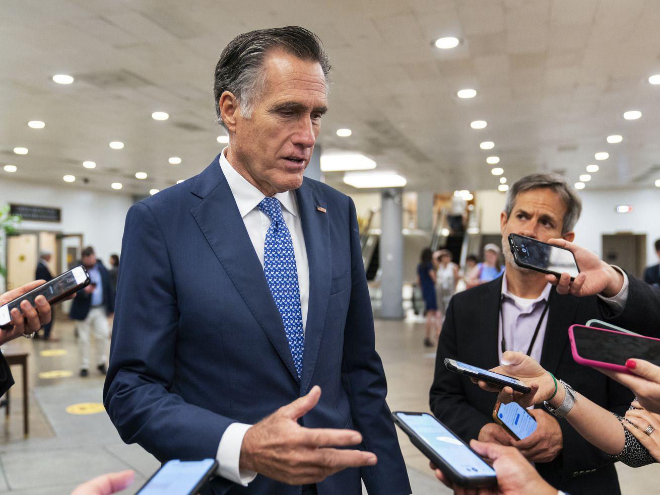 Sen. Mitt Romney, R-Utah, speaks to reporters as he walks on the Senate subway on Capitol Hill.