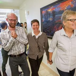 Derek Kitchen, Laurie Wood and Kody Partridge leave their press conference Monday, Oct. 6, 2014, in the office of Peggy Tomsic in Salt Lake City, after the Supreme Court refused to hear appeals on same sex marriages, making them legal.