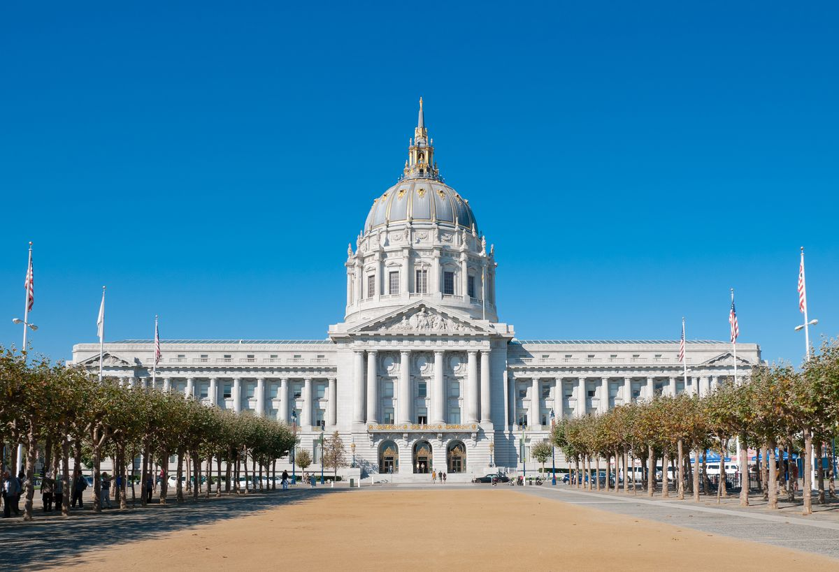 The exterior of San Francisco City Hall. The facade is white and there is a large dome with a gold top. In front of the building is a wide path lined with trees and flagpoles.