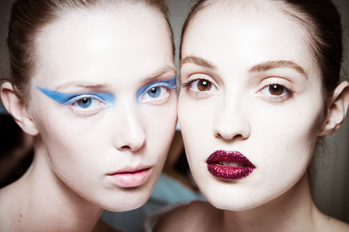 Close-up of two models, one with dramatic blue eyeshadow and the other with glittery lips