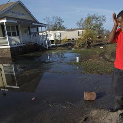 Ron Steward wipes his brow next to the house of his mother, Clara Williams, in Ironton, La., which was flooded from Hurricane Isaac, near Louisiana Hwy 23 in Plaquemines Parish, Monday, Sept. 3, 2012. The house was built seven years ago after her previous home was destroyed by Hurricane Katrina.
