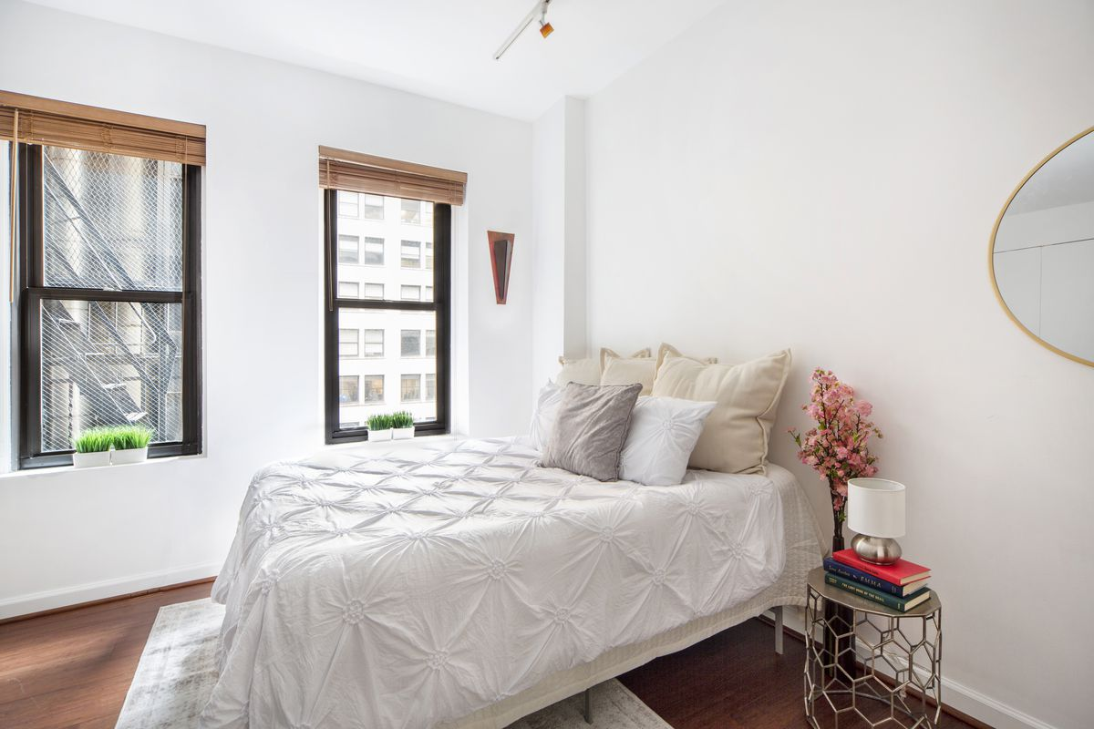 A bedroom with a medium-sized bed, two windows, white walls, and hardwood floors.