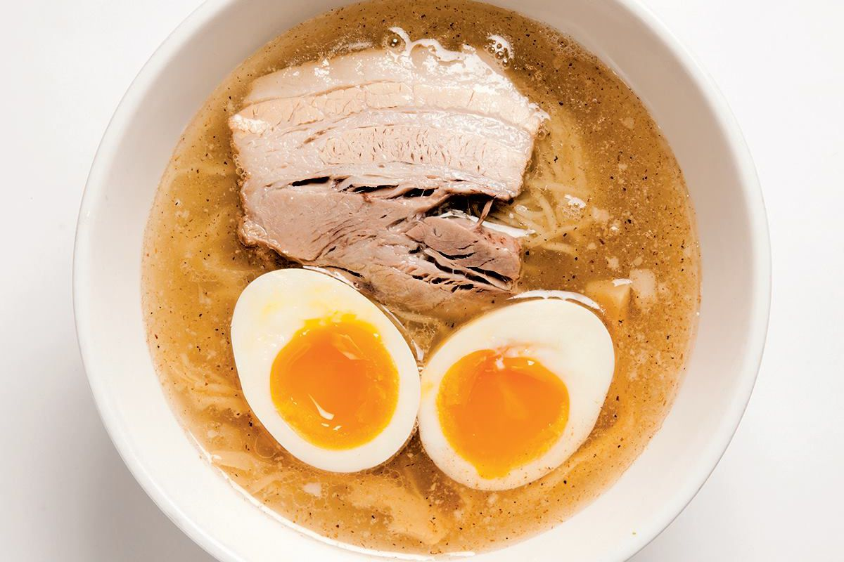 a top-view of a bowl full of ramen with a halved soft boiled egg and some slices of meat floating on top