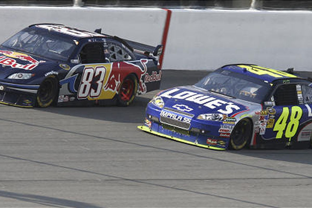 Brian Vickers (83) passes Jimmie Johnson (48) during the closing laps of the NASCAR Carfax 400 Sprint Cup Series auto race at Michigan International Speedway in Brooklyn, Mich., Sunday. Vickers won the race. Johnson ran out of gas.