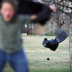 A trash can flies away as a Farmington Junior High student walks near the school during high winds in Farmington, Thursday, Dec. 1, 2011.