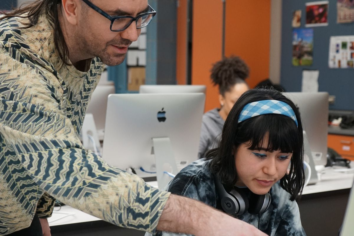 Jake Myers works with student Leni Bryan on a digital media assignment.