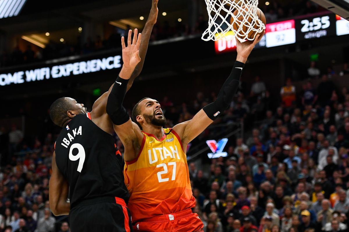 Rudy Gobert of the Utah Jazz attempts a shot under Serge Ibaka of the Toronto Raptors during a game at Vivint Smart Home Arena on March 9, 2020 in Salt Lake City, Utah.