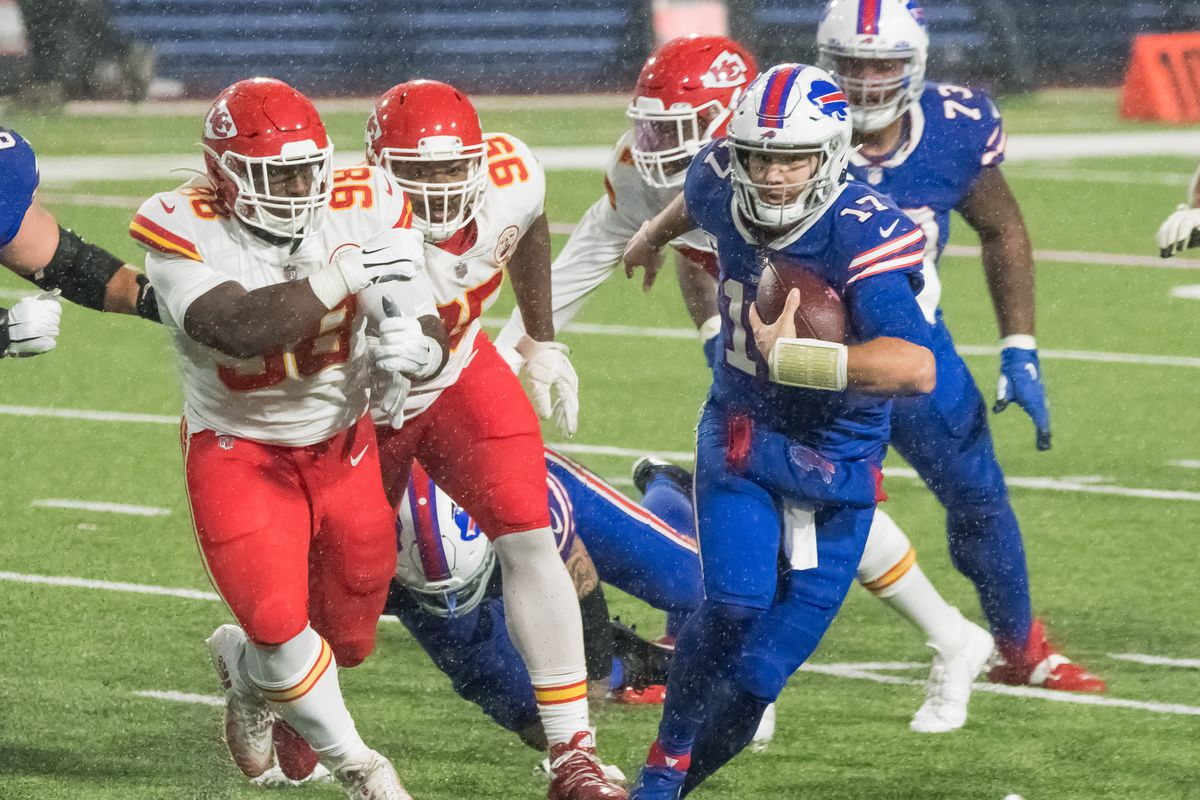 Buffalo Bills quarterback Josh Allen outruns Kansas City Chiefs defensive tackle Tershawn Wharton and defensive tackle Chris Jones  in the fourth quarter at Bills Stadium