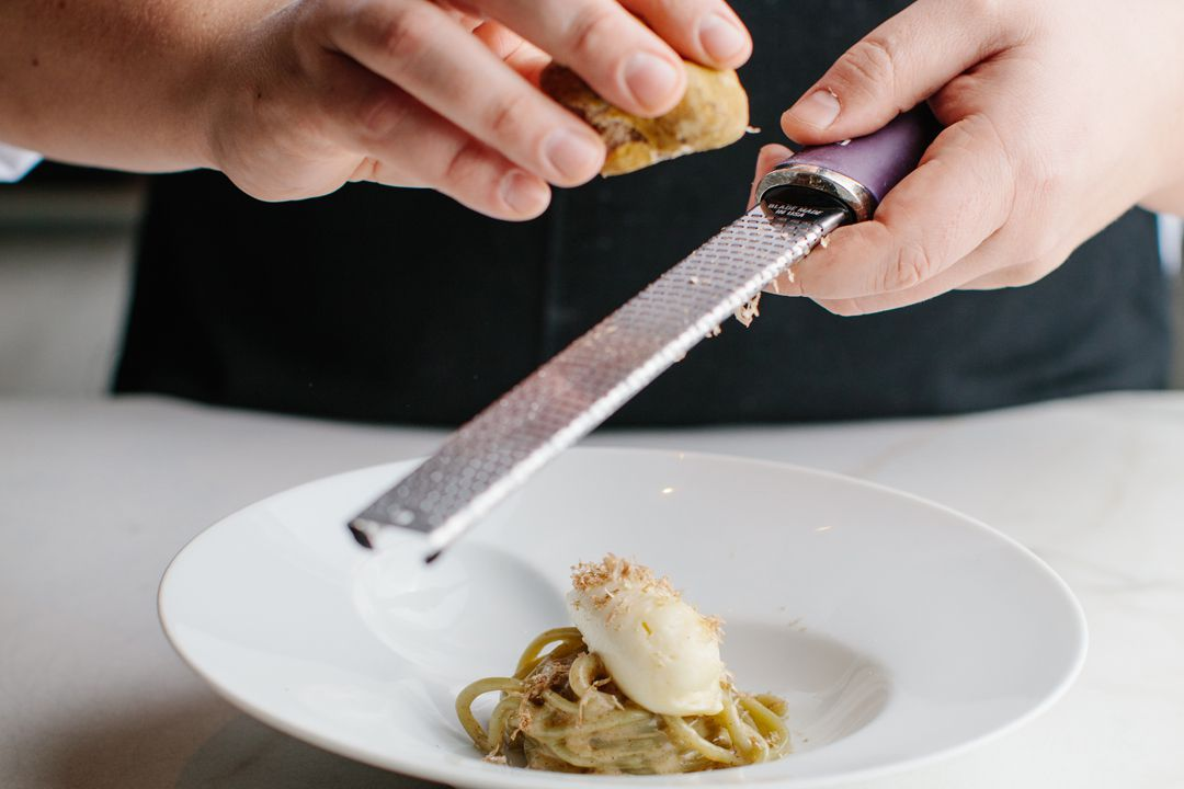 A person shaving a truffle over a plate of pasta.